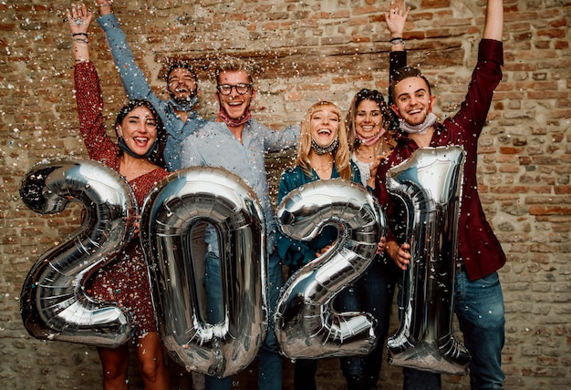 Feliz ano novo! grupo de jovens usando máscara facial comemorando 2021