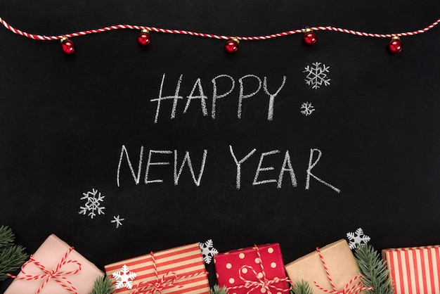 Feliz ano novo mão escrevendo texto no quadro-negro