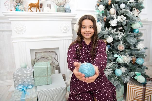 Feliz ano novo. menina criança gosta de presente de natal. natal. garoto aproveite o feriado. pequena menina feliz no natal. fones de ouvido quentes. na manhã antes do natal. feriado de ano novo. ótimo presente.