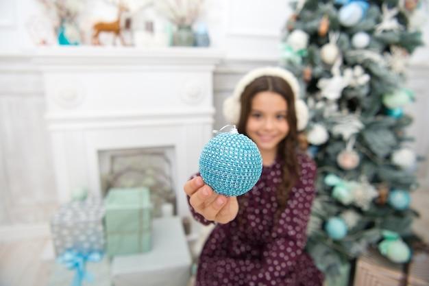 Feliz ano novo. natal. garoto aproveite o feriado. pequena menina feliz no natal. na manhã antes do natal. feriado de ano novo. menina criança gosta de presente de natal. decorar a árvore de natal.
