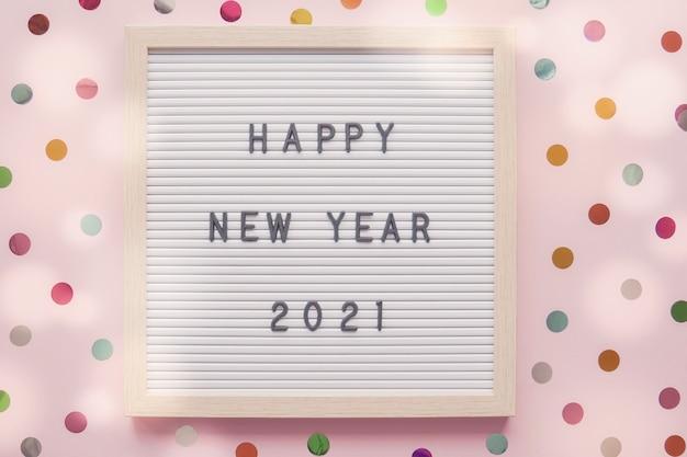 Feliz ano novo no quadro de correspondência com fundo pastel rosa de pontos coloridos