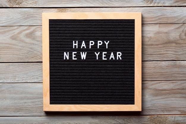 Feliz ano novo palavras em uma placa de carta com fundo de madeira