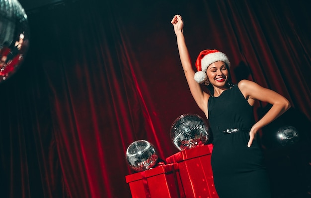 Feliz ano novo pra você! morena lindas mulheres sexy com chapéu de papai noel e vestido preto. festa de ano novo. noite de natal. no contexto das caixas de presente vermelhas e bolas de discoteca.