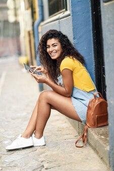 Feliz, árabe, mulher, sentando, ligado, urbano, passo, com, um, tablete digital