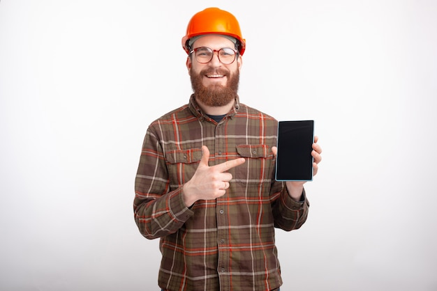 Feliz arquiteto barbudo está apontando para um tablet eletrônico com tela em branco no espaço em branco.