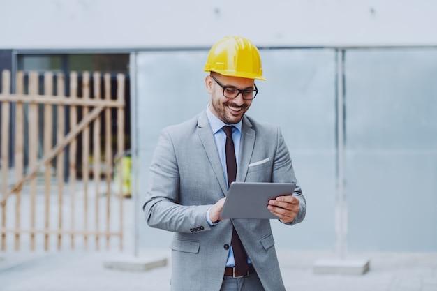 Feliz arquiteto caucasiano de terno e com o capacete na cabeça, usando o tablet em pé no canteiro de obras.