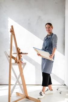 Feliz artista segurando tela pintada