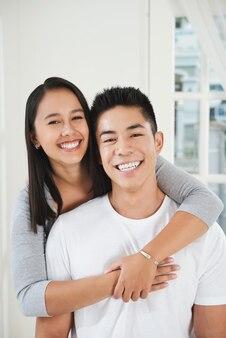 Feliz asiático jovem abraçando e olhando para a câmera