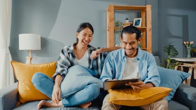Feliz asiático jovem casal atraente, homem e mulher, sentados no sofá, usam tablet para comprar móveis online em uma casa nova
