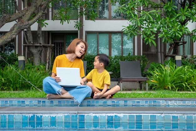 Feliz, asiático, mãe filho, usando computador portátil, em, ao ar livre, piscina
