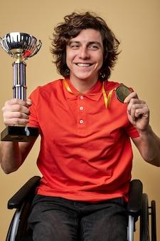 Feliz atleta paralímpico em cadeira de rodas segurando um cálice de campeão e medalhas de ouro isoladas em fundo bege