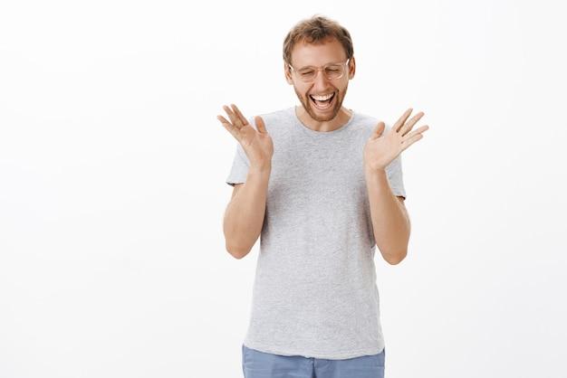 Feliz atraente aduly europeu com cerdas fechando os olhos triunfando e celebrando notícias fantásticas gritando de felicidade e acenando com as mãos levantadas emocionado