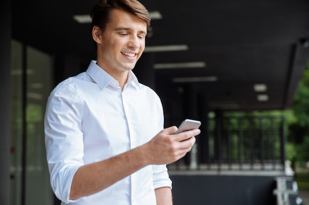 Feliz atraente jovem empresário usando smartphone e sorrindo perto do centro de negócios