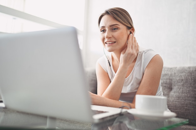 Feliz atraente jovem estudante estudando on-line em casa, usando o computador portátil, fones de ouvido, conversando com vídeo, acenando. trabalho remoto, educação a distância. videoconferência ou evento virtual em quarentena
