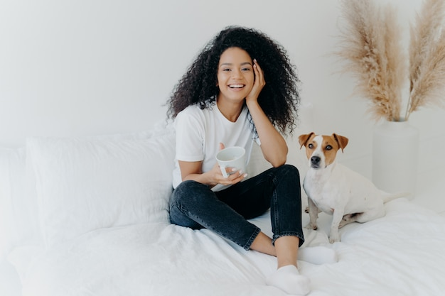 Feliz atraente mulher étnica com cabelos cacheados veste camiseta branca, calça jeans e meias, sorri agradavelmente, bebe chá na cama confortável, posa com cachorro, tem um fim de semana preguiçoso. pessoas, descanso, conceito de animais