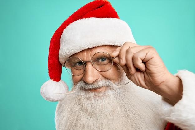Feliz autêntico papai noel com chapéu vermelho e óculos posando para crianças.