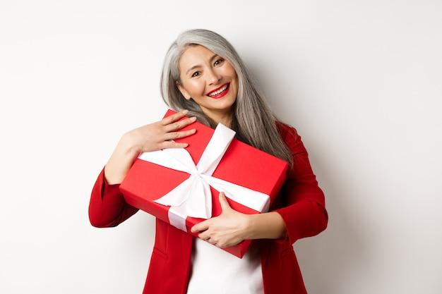 Feliz avó asiática abraçando a caixa de presente vermelha e sorrindo, agradecida, agradecendo pelo presente, em pé sobre um fundo branco.