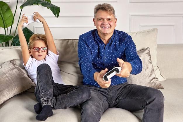 Feliz avô joga videogame com o neto usando o joystick na sala de estar.