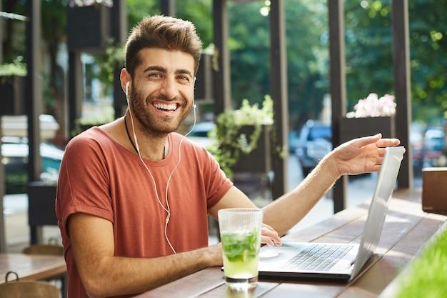 Feliz barbudo bonito usando fones de ouvido usando laptop em um café ao ar livre, sorrindo alegremente