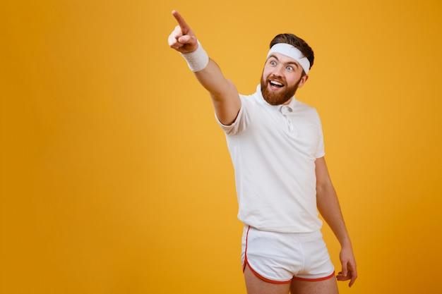 Feliz barbudo esportista apontando para fora