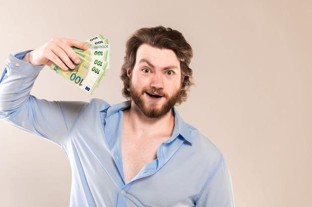 Feliz barbudo jovem segurar notas de dinheiro de 100 euros em dinheiro isoladas em um fundo cinza.