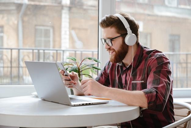 Feliz barbudo jovem usando música móvel e ouvir.