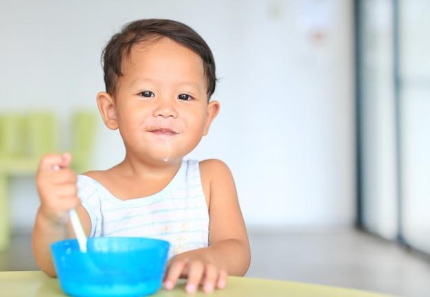 Feliz bebê asiático menino comer cereais com flocos de milho e manchas de leite na boca em cima da mesa