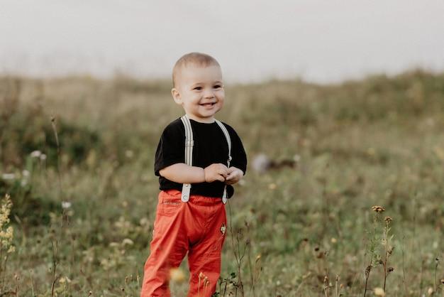 Feliz bebê menino bonitinho sorrindo no campo