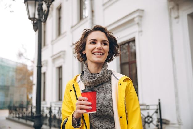 Feliz bela jovem bebendo café. olhando de lado.