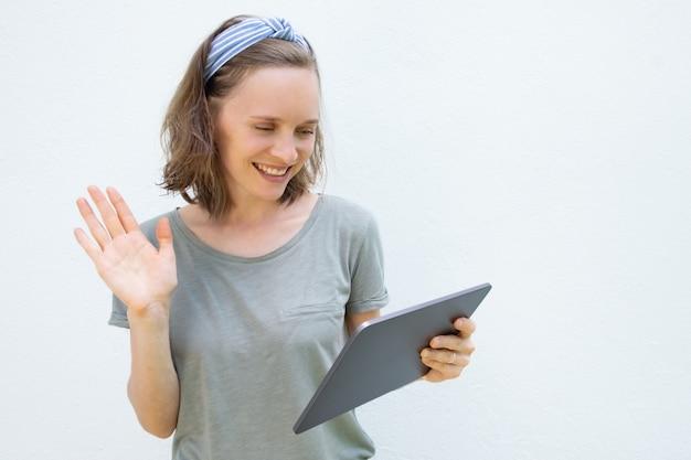 Feliz bela jovem com tablet acenando olá em exposição