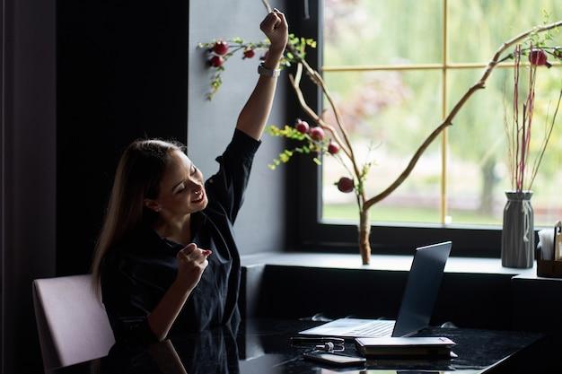 Feliz bem sucedida mulher de negócios bem jovem vestindo camisa preta elegante com laptop e diário sentado no local de trabalho e comemorando a vitória.