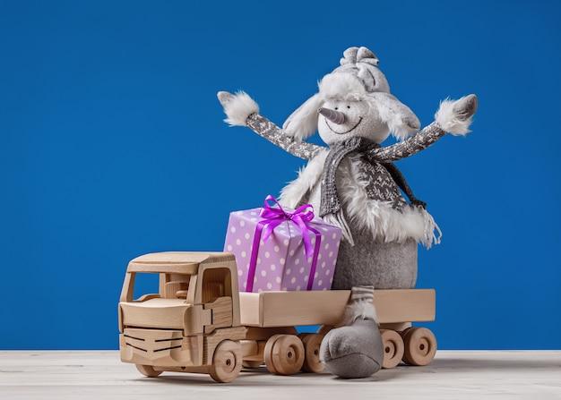 Feliz boneco de neve com presentes de natal no caminhão de brinquedo.