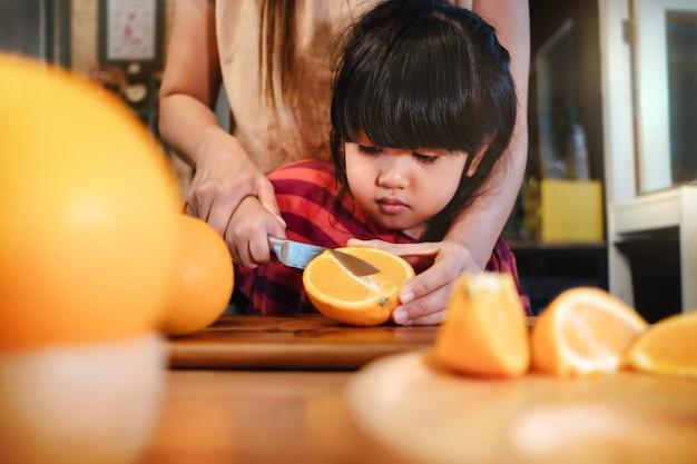 Feliz bonito 3-4 anos velha com sua fatia de mãe um pouco de laranja na mesa de madeira na despensa. a rapariga está aprendendo o cozinheiro com sua matriz. frutas e vegetais para o conceito de crianças
