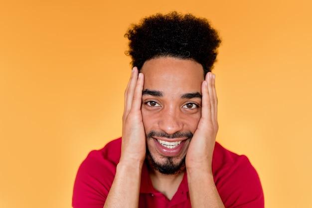 Feliz bonito homem afro-americano vestindo camiseta vermelha, sorrindo por cima da parede laranja.
