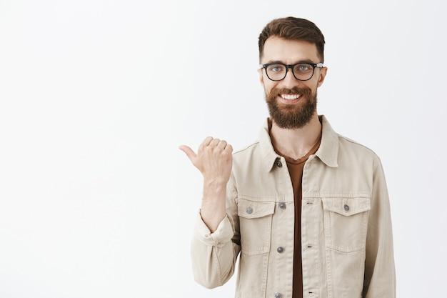 Feliz bonito homem barbudo de óculos posando contra a parede branca