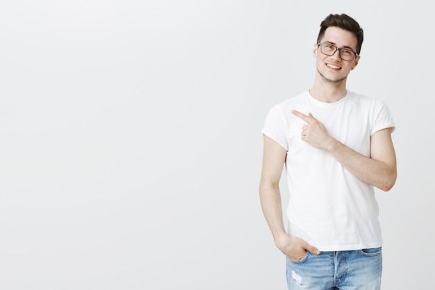 Feliz bonito jovem estudante de óculos apontando o dedo esquerdo para copyspace