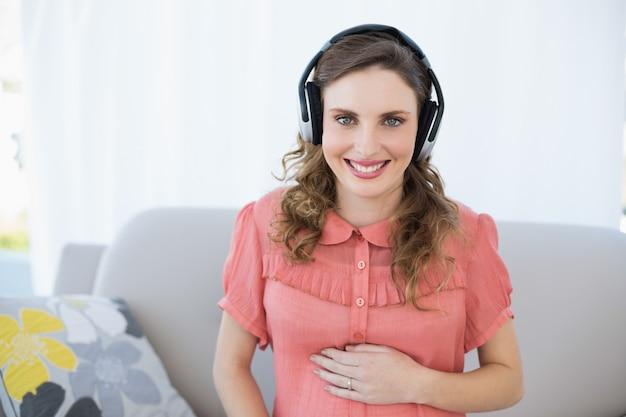 Feliz, bonito, mulher grávida, relaxante, em, a, sala de estar, escutar música