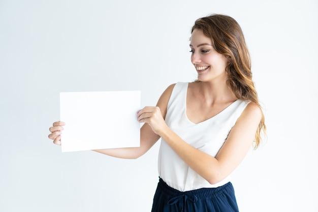 Feliz, bonito, mulher jovem, mostrando, folha em branco, de, papel
