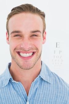 Feliz bonito na camisa na frente do teste do olho