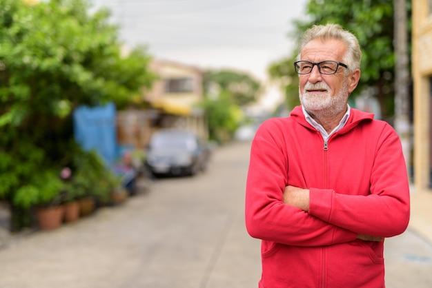 Feliz bonito sênior barbudo sorrindo e pensando enquanto usava óculos com os braços cruzados ao ar livre