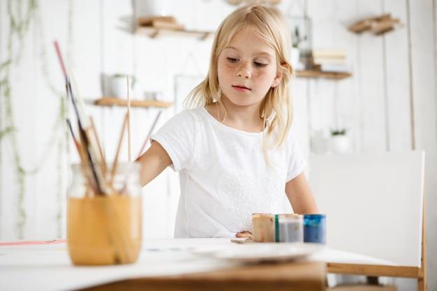Feliz, brincalhão e fofa menina loira com sardas e lindos olhos azuis, vestida de camiseta branca, mordendo o pincel