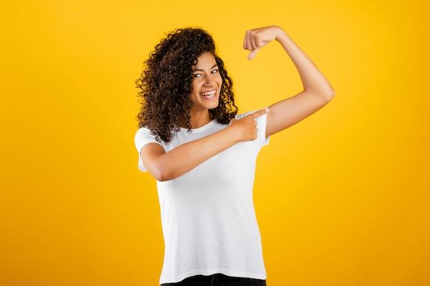 Feliz cabe garota negra mostrando bíceps isolado sobre amarelo