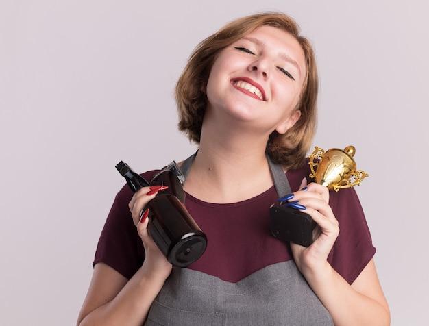 Feliz cabeleireira jovem bonita com avental segurando um troféu de ouro e um frasco de spray com aparador sorrindo com os olhos fechados em pé sobre uma parede branca