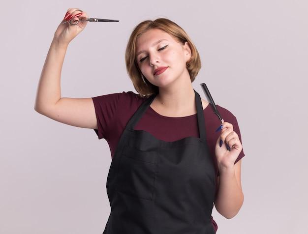 Feliz cabeleireira jovem bonita com avental segurando uma tesoura e um pente de cabelo com os olhos fechados, sorrindo em pé sobre uma parede branca