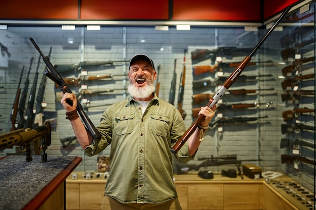 Feliz caçador masculino com dois rifles na loja de armas. interior da loja de armas, variedade de munições e munições, escolha de armas de fogo, hobby de tiro e estilo de vida