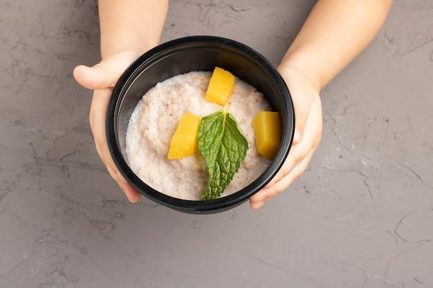 Feliz café da manhã saudável. garoto mãos segurando uma tigela de mingau de cereais, com flocos de aveia, sementes de chia, frutos secos amarelos. vista de cima