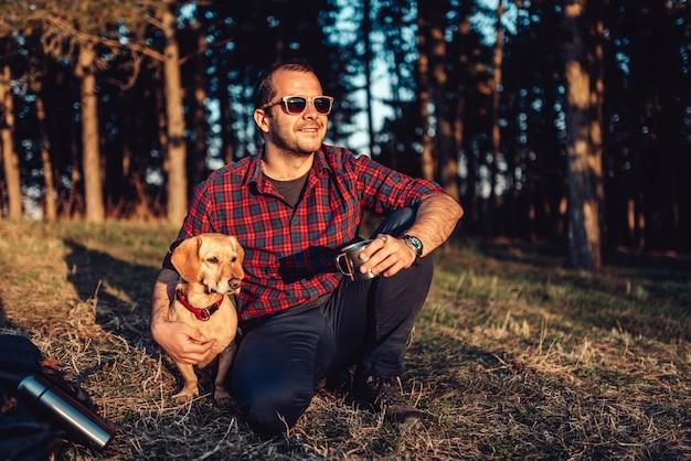 Feliz caminhante com cachorro descansando na grama e tomando café