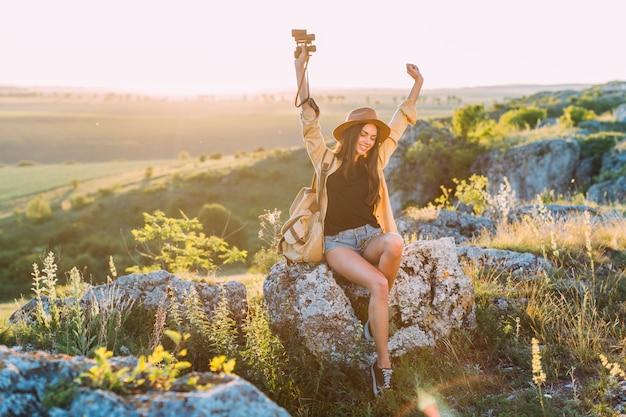 Feliz caminhante feminino sentado na rocha, levantando as mãos