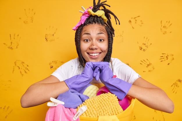 Feliz, cansada, mas satisfeita, mulher afro-americana usa luvas de borracha inclinada para o cesto de roupa suja lava tudo ao redor isolado sobre a parede amarela
