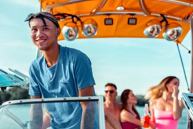 Feliz capitão. jovem afro-americano com uma bandana preta na cabeça, dirigindo um barco de recreio com os amigos